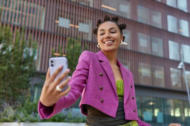 머리에 만두를 한 소녀가 스마트폰 카메라를 긍정적으로 바라보며 화상 통화에서 말하는 미소를 지으며 무선 인터넷에 연결된 현대적인 도시 건물을 배경으로 셀카를 찍습니다.