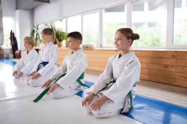 Девушка с пучками волос улыбается во время тренировки с друзьями