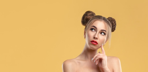 Girl with hair buns wearing red dress holding smartphone and thinking with copy space on yellow wall