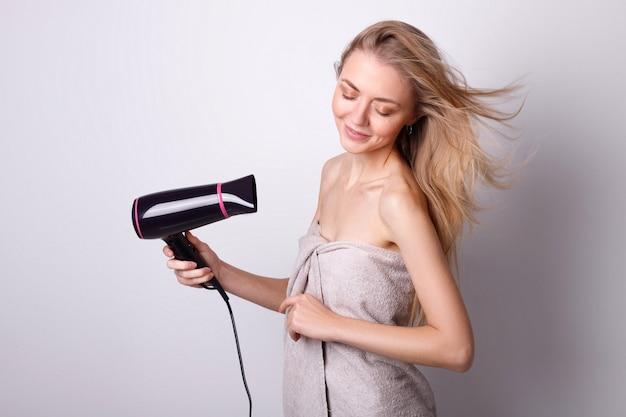 白い壁にヘアドライヤーを持つ少女。美しい強い髪。ヘアケア
