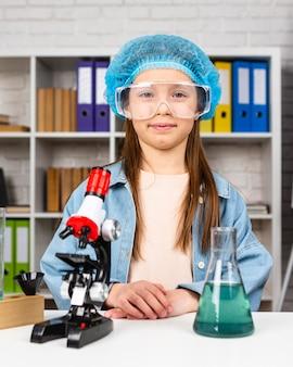 Ragazza con retina per capelli e occhiali di sicurezza facendo esperimenti scientifici