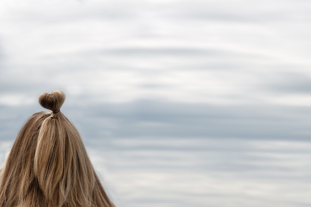 Girl with hairstyle in the form of a heart on the background of the sea, sky.