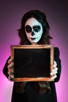 Girl with halloween makeup holding slate