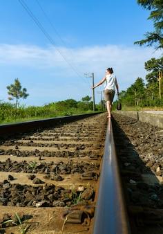 손 가방 철도 라인에 걷는 여자 프리미엄 사진