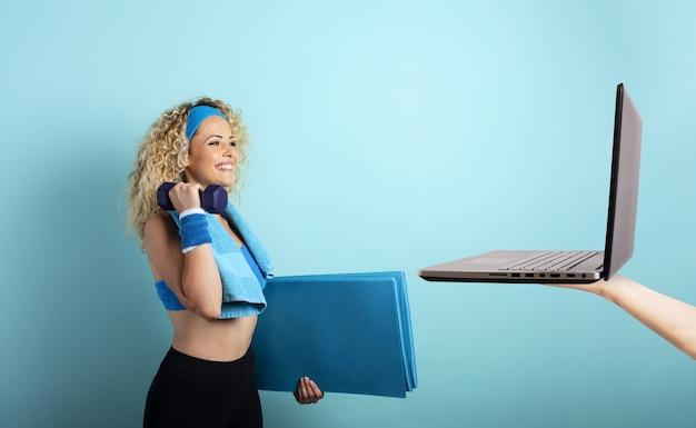 コンピューターを使ってオンラインでジムを始める準備ができているハンドルバーを持つ少女。シアンの壁