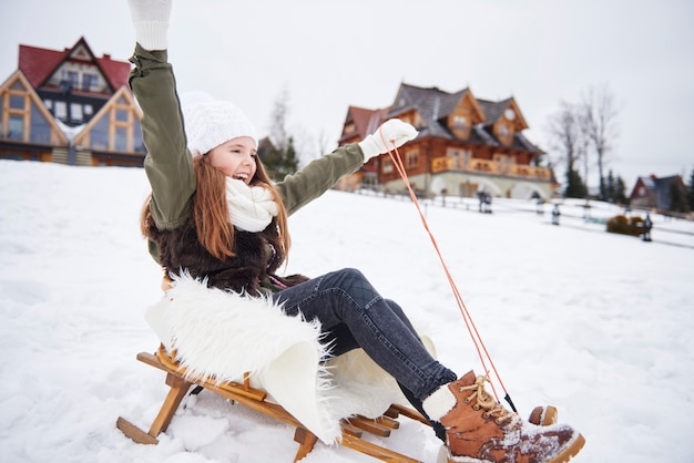 Girl with hands raised on a sleigh