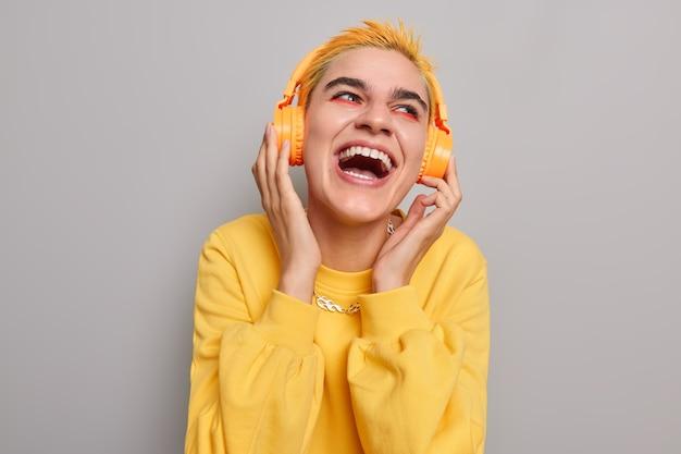 Девушка со счастливым выражением лица слушает любимый трек в наушниках с сияющей зубастой улыбкой, одетая в повседневный джемпер, позирует на сером