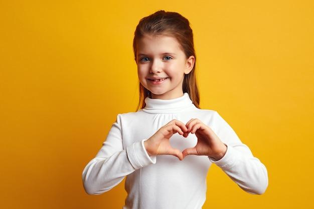 Девушка со счастливой улыбкой формирует сердце обеими руками и выражает любовь к вам