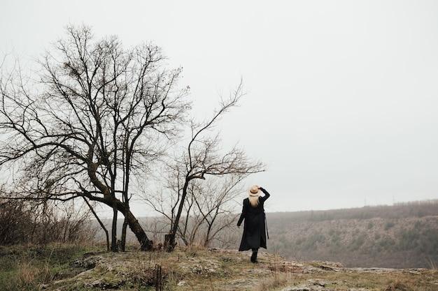 모자와 검은 코트를 입은 소녀는 높은 산의 풍경을 존경합니다.
