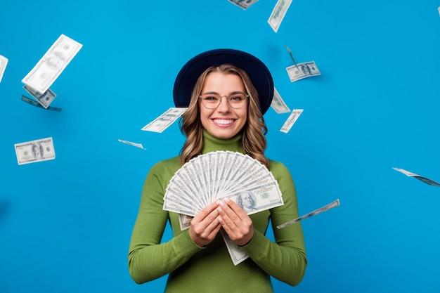 Девушка в шляпе и очках держит веер с деньгами