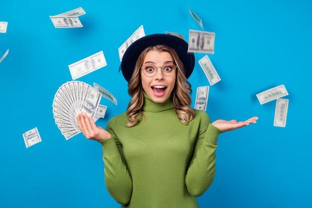 お金のファンを保持している帽子とメガネの女の子