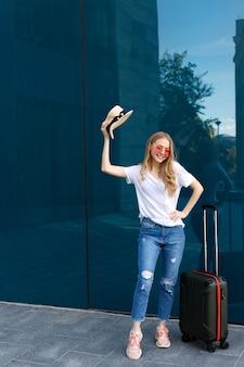 모자와 파란색 배경에 수하물 행복 소녀와 여행