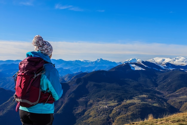 Girl with hat and backpack looking at snowy mountains.