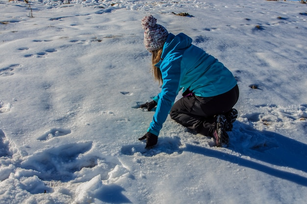 山の地面から雪をキャッチする帽子の少女。