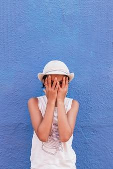 彼女の顔の色の背景を覆う帽子を持つ少女