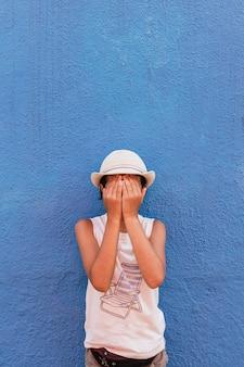 彼女の顔を覆う帽子を持つ少女