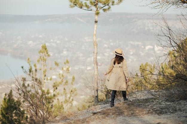 모자 소녀는 언덕에서 마을의 파노라마를 즐길 수 있습니다.