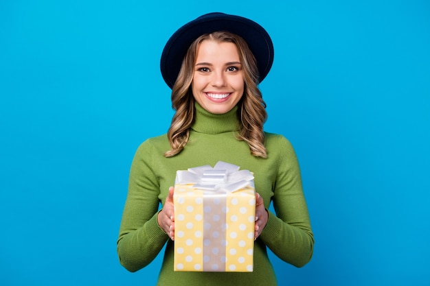 Girl with hat and glasses holding gift isolated on blue