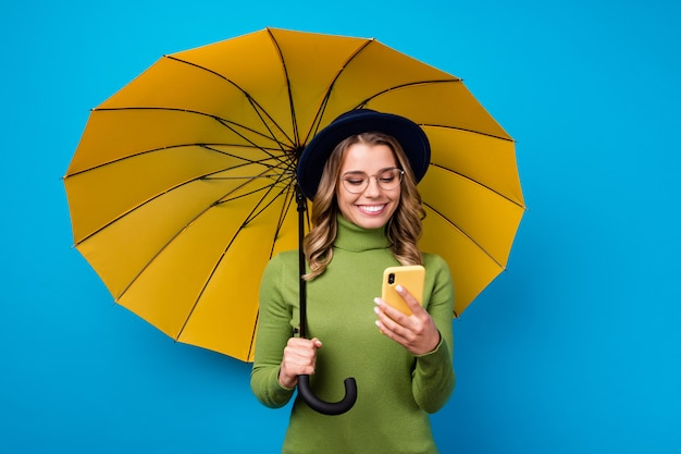 Girl with hat and glasses holding umbrella and phone