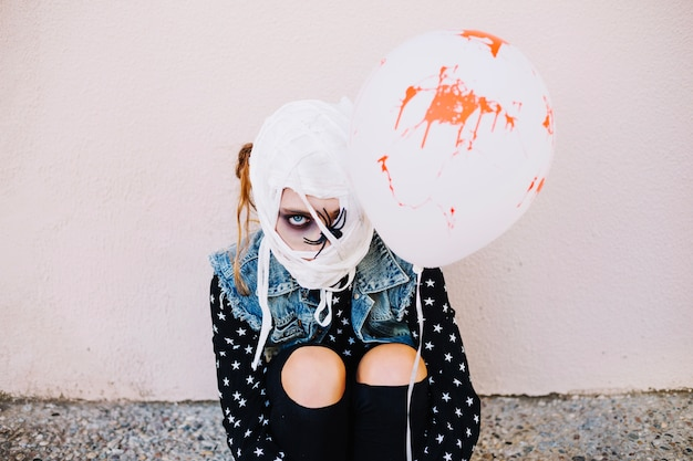 Girl with head bandaged holding blood balloon