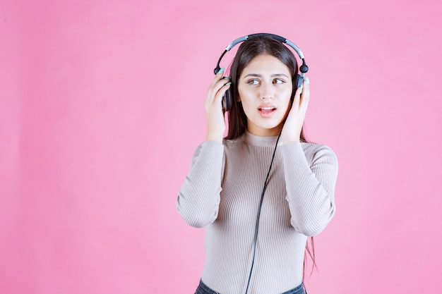 Girl with headphones checking the music and looks serious