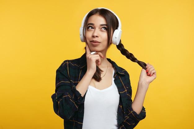 Девушка в наушниках наслаждается звуком музыки, держа руку на подбородке