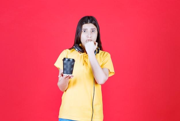 黒い使い捨ての飲み物を持っているヘッドフォンを持った少女は、怖くて怖がっているように見えます。