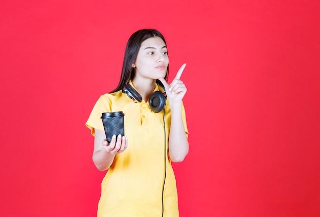 黒い使い捨ての飲み物を持っているヘッドフォンを持つ少女。