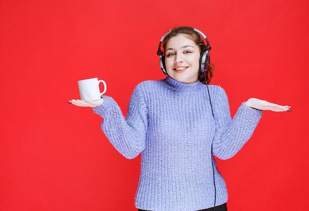 Девушка с наушниками держит кружку кофе и улыбается.
