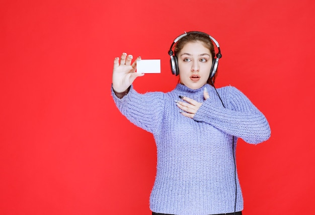 Girl with headphones holding a business card and looks surprized.