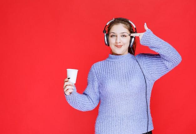 Ragazza con le cuffie che tiene una tazza di caffè e pensa.