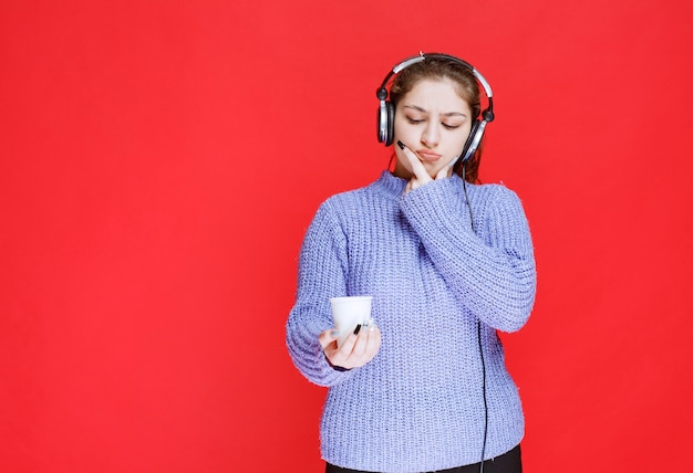 Girl with headphones holding a coffee cup and thinking.
