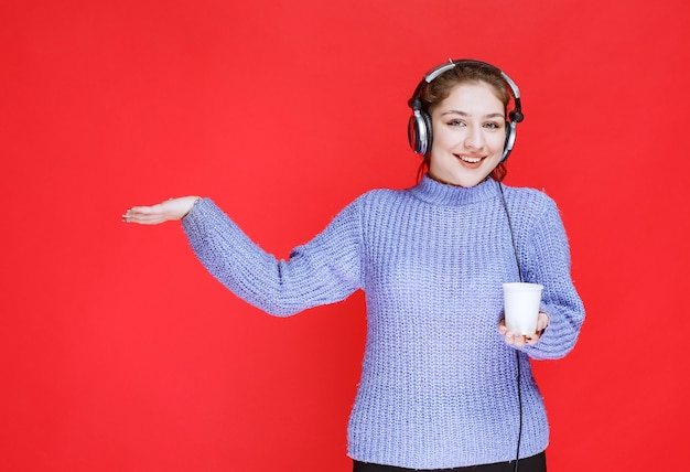Girl with headphones holding a disposable cup of coffee.