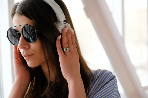 Girl with headphones listening to music, at the airport, office. young woman with glasses.