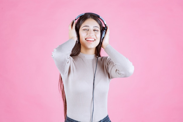 Girl with headphones listening the music and feeling happy
