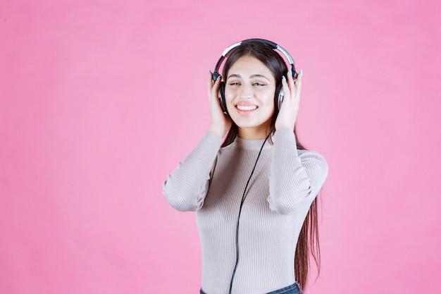 Девушка в наушниках слушает музыку и чувствует себя счастливой