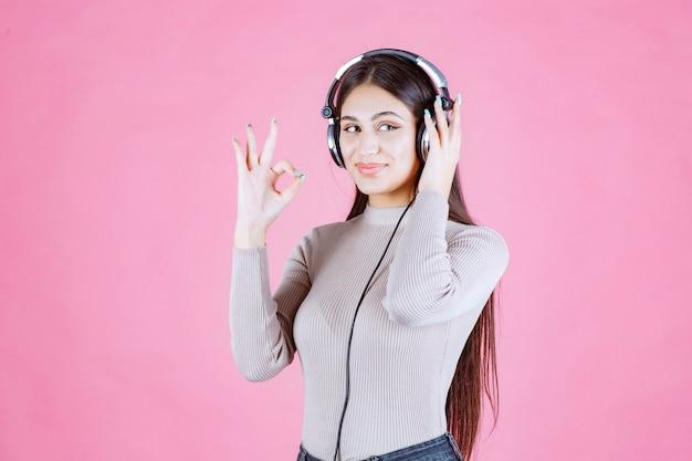 Девушка в наушниках слушает музыку и показывает свое удовольствие