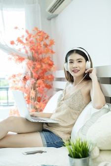 Девушка с наушниками слушает музыку в ноутбуке на кровати у себя дома
