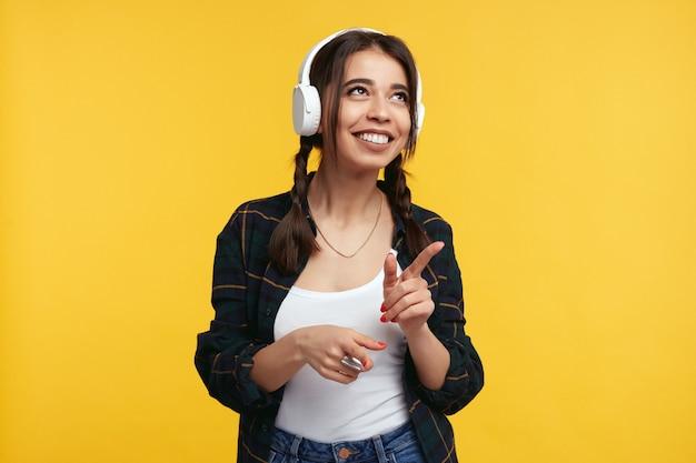 Девушка в наушниках слушает музыку и улыбается над желтой стеной