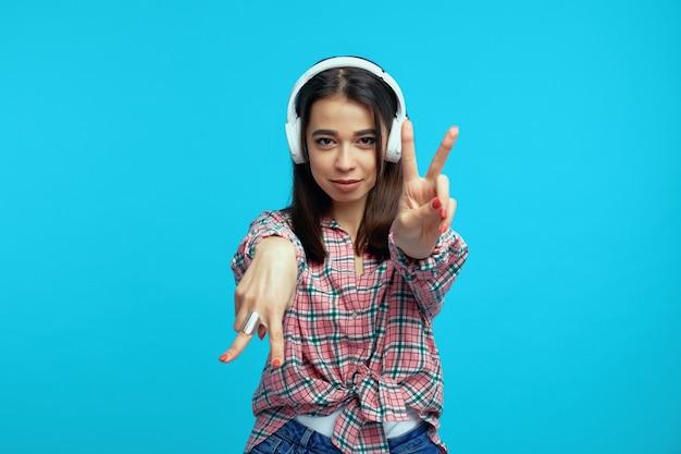 Девушка в наушниках слушает музыку во время танца и показывает жест мира