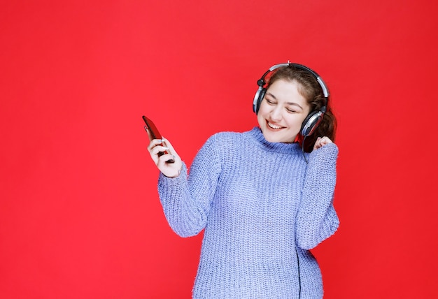 Girl with headphones making a video call and saying hello.