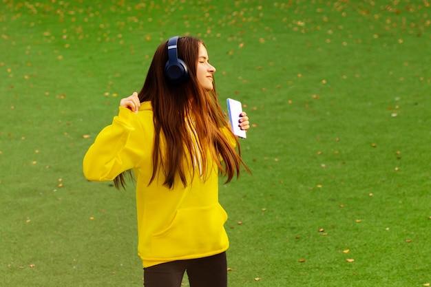 Девушка с наушниками на зеленом поле в желтой толстовке с капюшоном танцует, слушает музыку