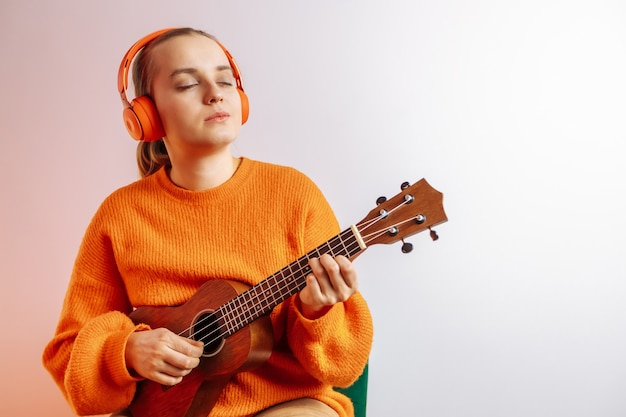 A girl with headphones plays the ukulele