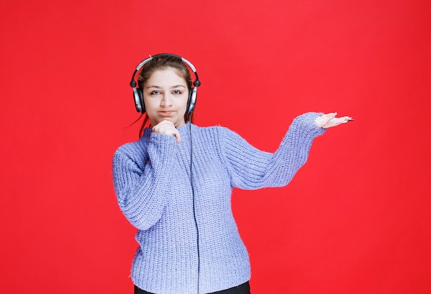 Girl with headphones pointing at something on the right.