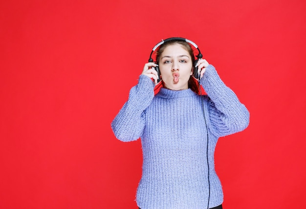 Girl with headphones putting her tongue out.