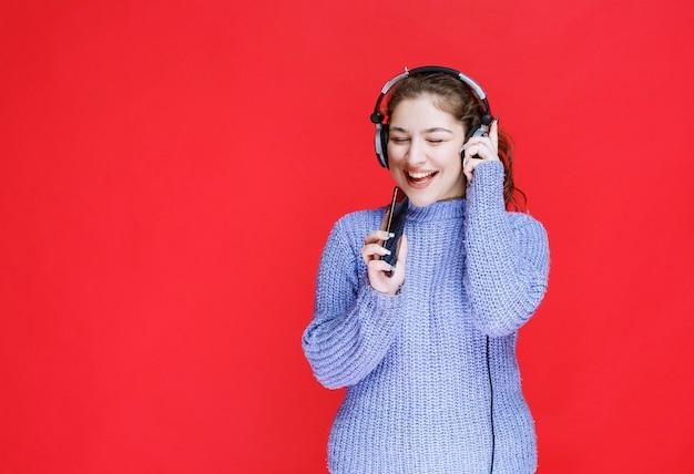 Девушка с наушниками устанавливает музыку на свой смартфон и наслаждается ею.