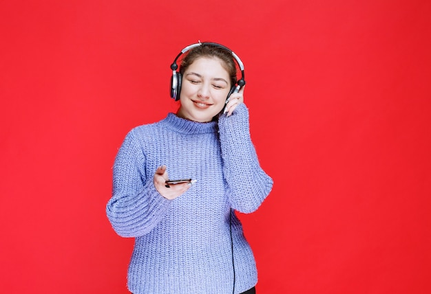 Girl with headphones setting music at her smartphone and enjoying it.