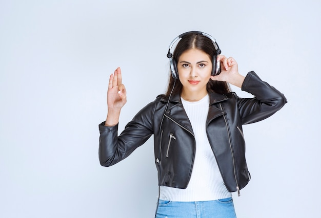 楽しみのサインを示すヘッドフォンを持つ少女。