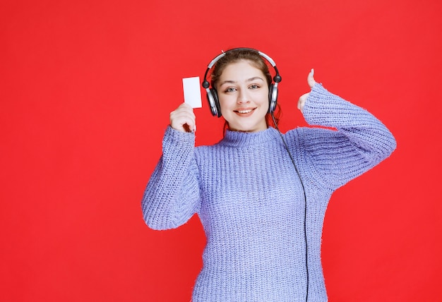Girl with headphones showing her business card and making satisfaction sign.