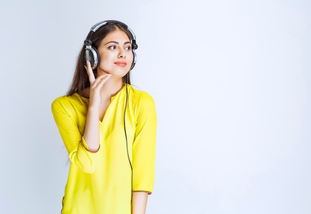 落ち着いて音楽を楽しんでいるヘッドフォンを持つ少女。
